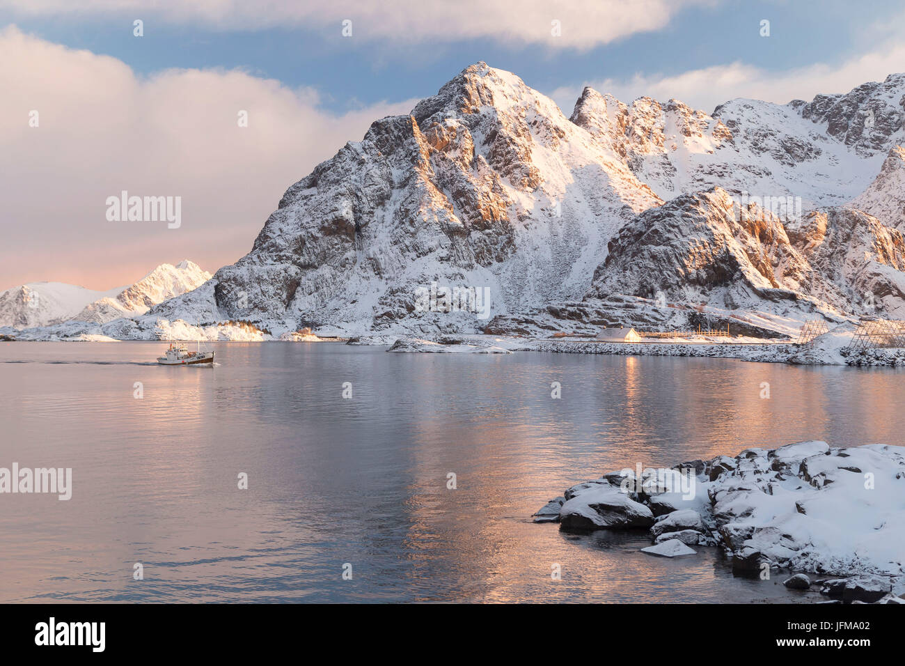 Snowy mountains edging the icy waters of Henningsvær Fishing village, Lofoten Islands, Norway - Stock Image