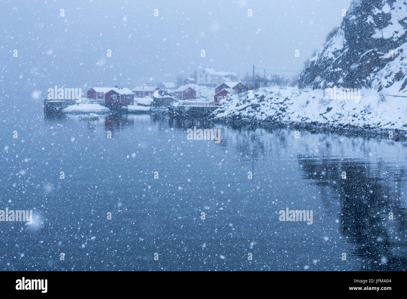 Snowfall in a small bay of Nusfjord fishing village, Lofoten Islands, Norway - Stock Image