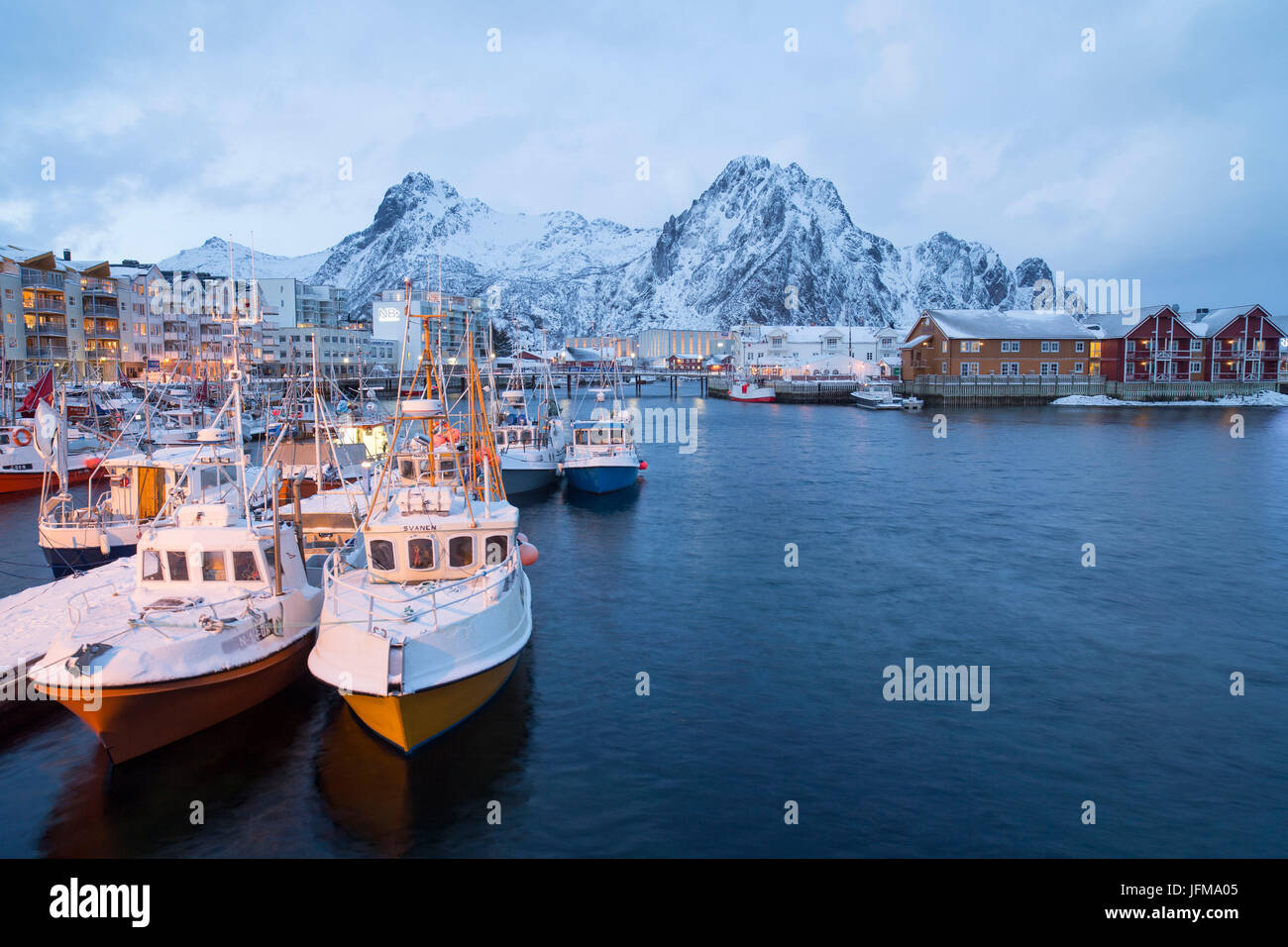 Fishing boats lined up in The port of Henningsvær Fishing Village, Lofoten Islands, Norway - Stock Image