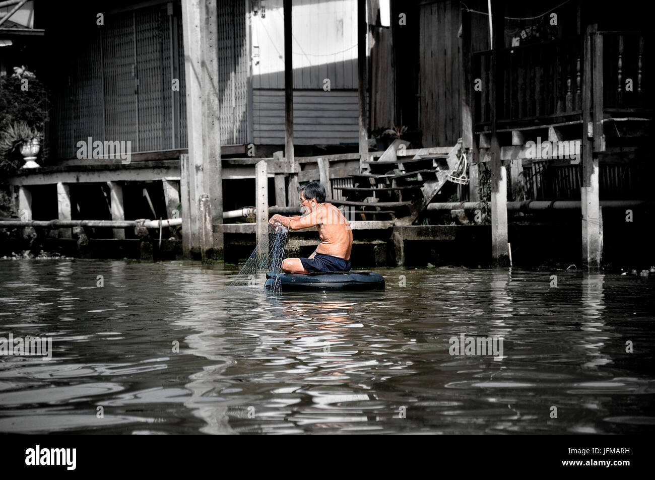 A Chinese fisherman who patiently and quietly waiting for its prey floating on an old inner tube - Stock Image