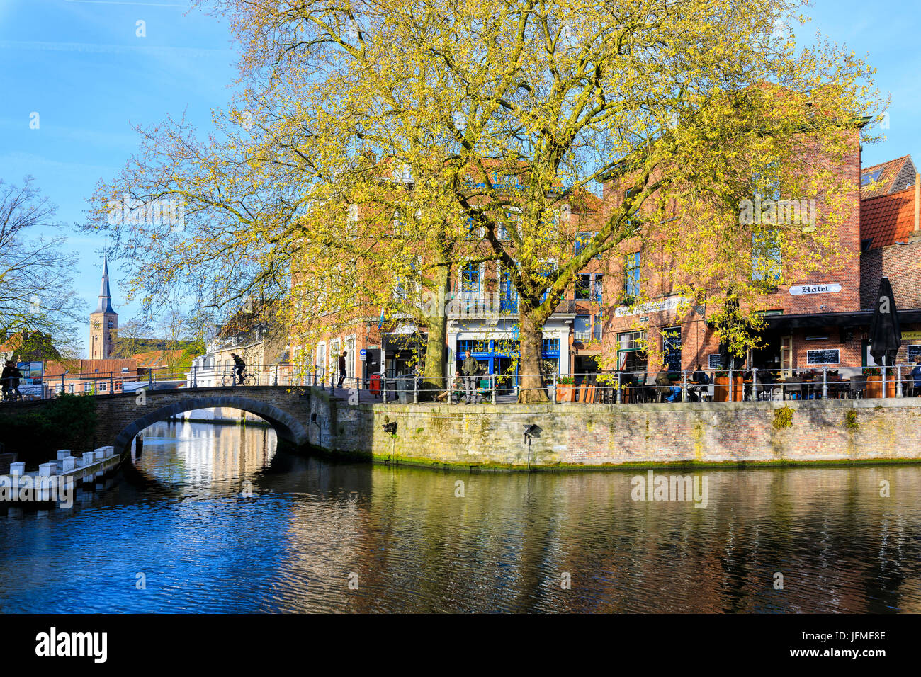 Spring sun on the medieval buildings of the city centre framed by bridges and typical canals Bruges West Flanders - Stock Image