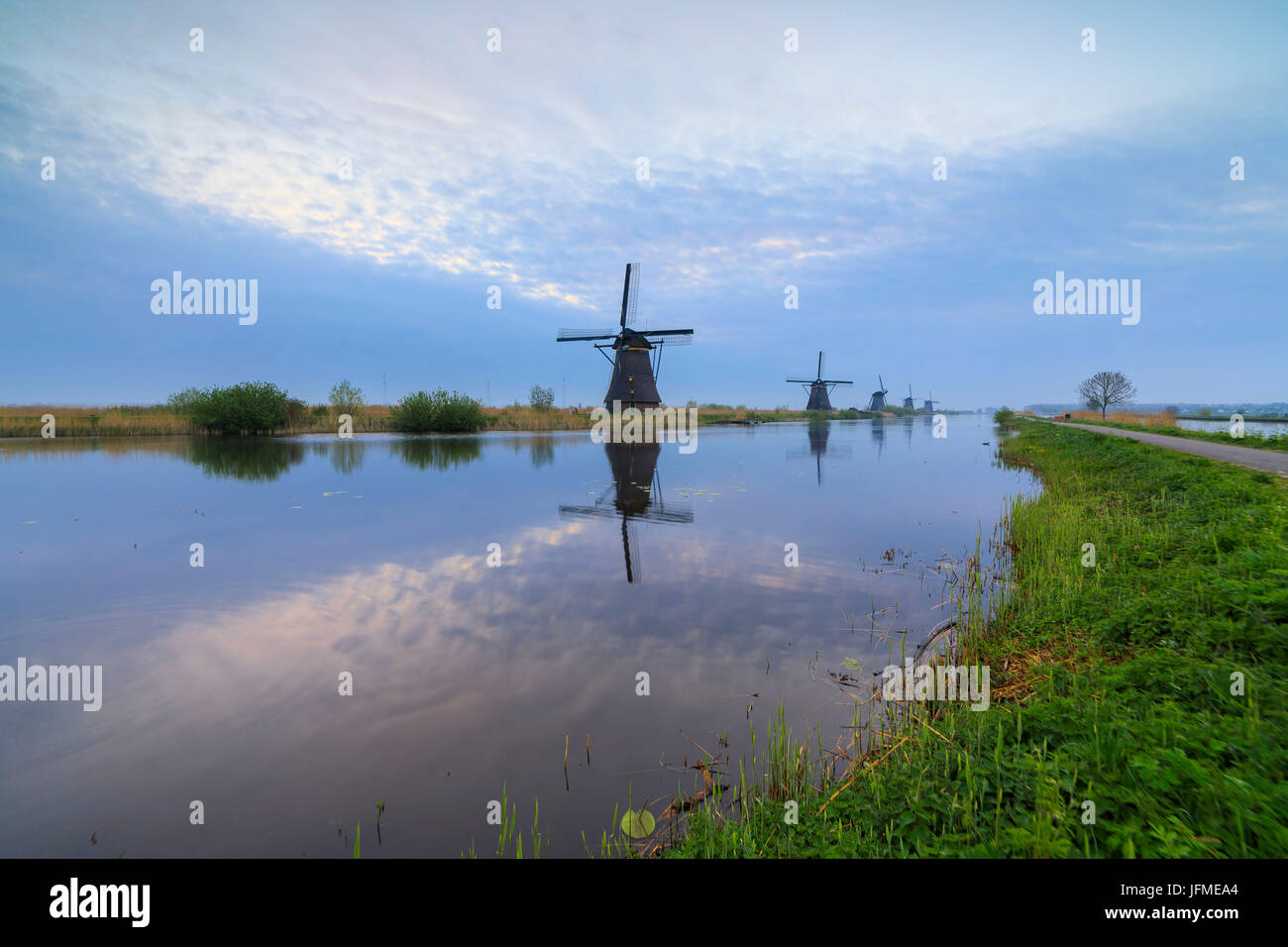 Traditional Dutch windmills reflected in the canal at dusk Kinderdijk Molenwaard South Holland The Netherlands Europe Stock Photo