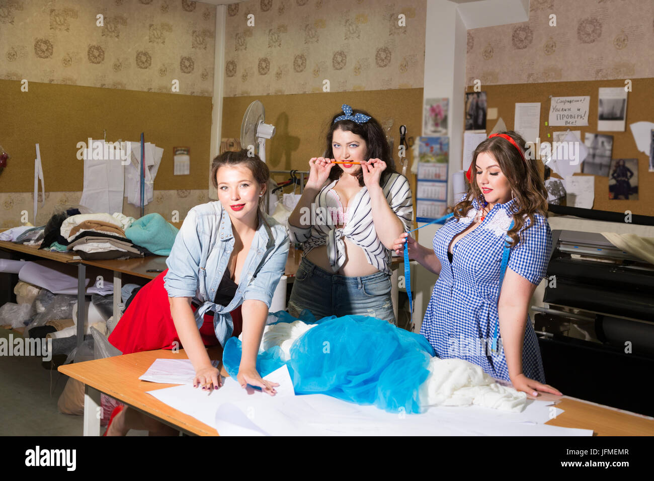 c9eca6f75e0 Beautiful curvy female models imagined as pinup seamstresses at a clothing  workshop - Stock Image