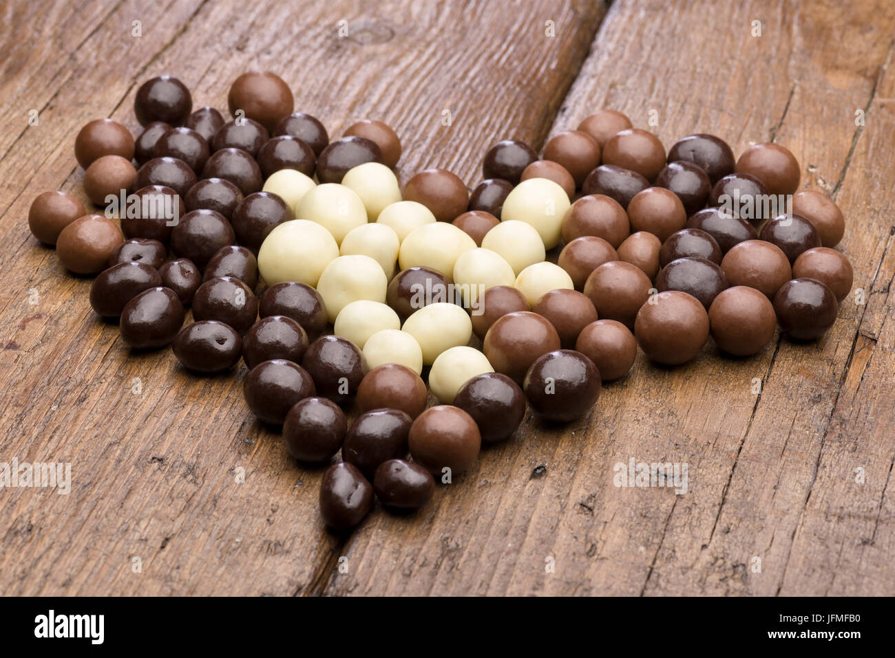 heap of assorted chocolate pralines on wooden table - Stock Image