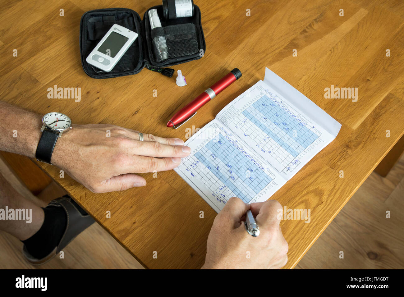Diabetic make notes in  his blood glucose test book, notes about blood glucose levels, diary, - Stock Image