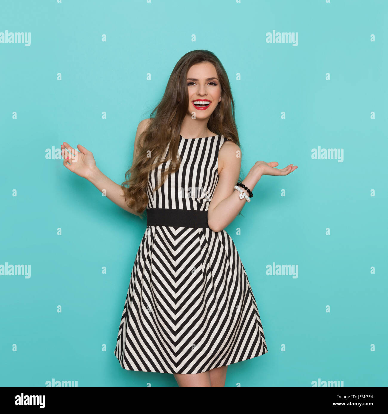 d1376f984f2 Smiling attractive woman in black and white striped dress standing with  arms outstretched and looking at camera. Three quarter length studio shot  on t
