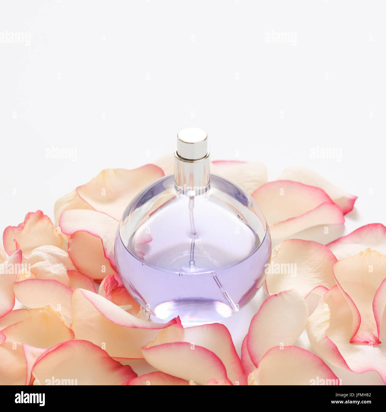Perfume bottle with flower petals on light background. Perfumery, fragrance collection. Women accessories. - Stock Image