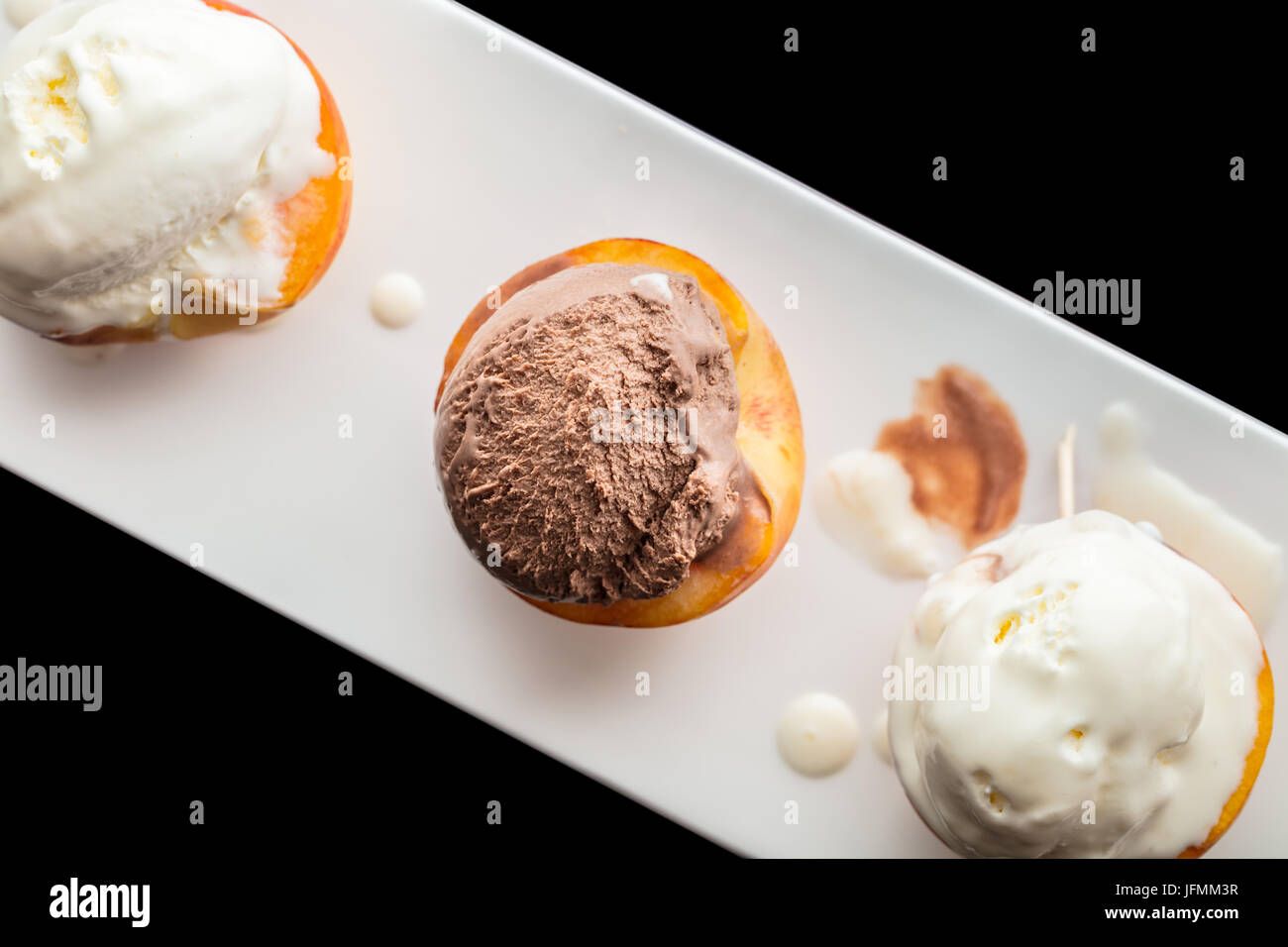 Dessert ice cream on peach, black background - Stock Image