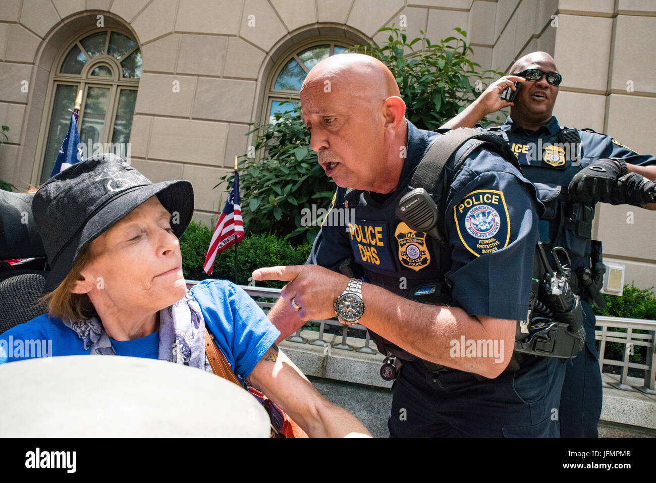 A Federal Police officer confronts disability rights activist, Cathleen Holdsworth in front of Senator Pat Toomey's - Stock Image