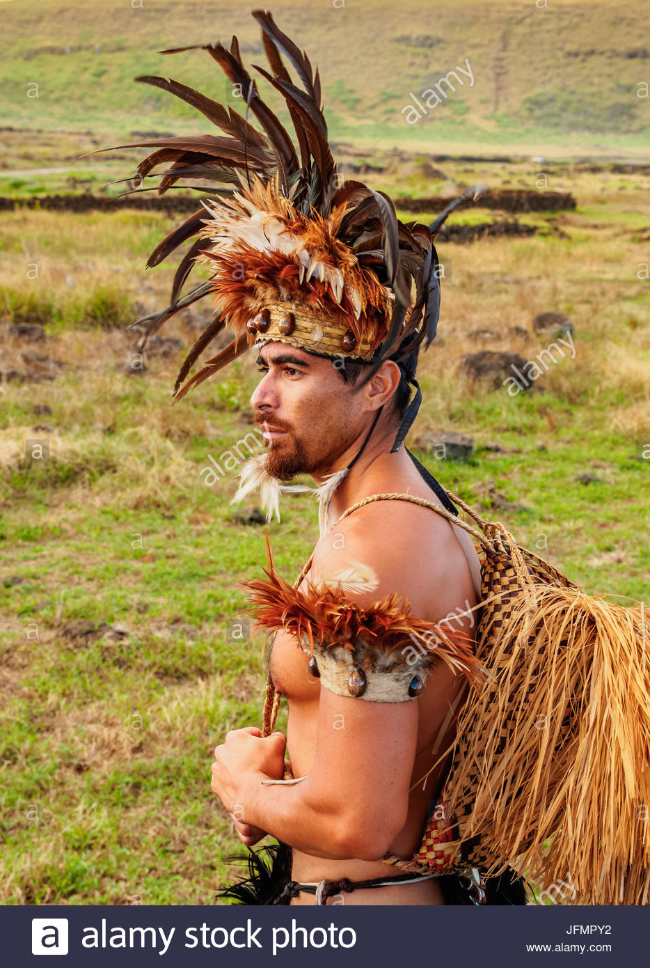 Native Rapa Nui man in tradititional costume at Ahu Tongariki, Rapa Nui National Park, Easter Island, Chile. MR - Stock Image
