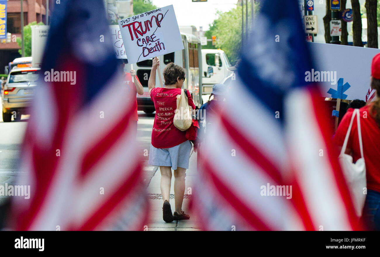 A woman carries a sign during a march to the Philadelphia offices of Senator Pat Toomey, opposing his support for - Stock Image