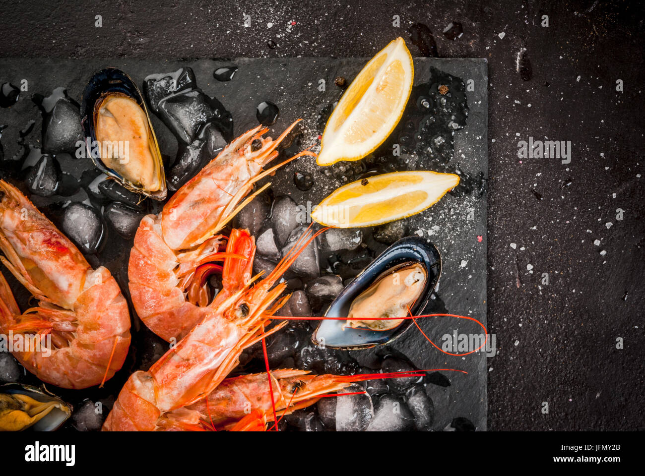 Prepared for cooking dinner seafood - shrimp and mussels on ice, on a cutting slate board, with lemon and seasonings. - Stock Image