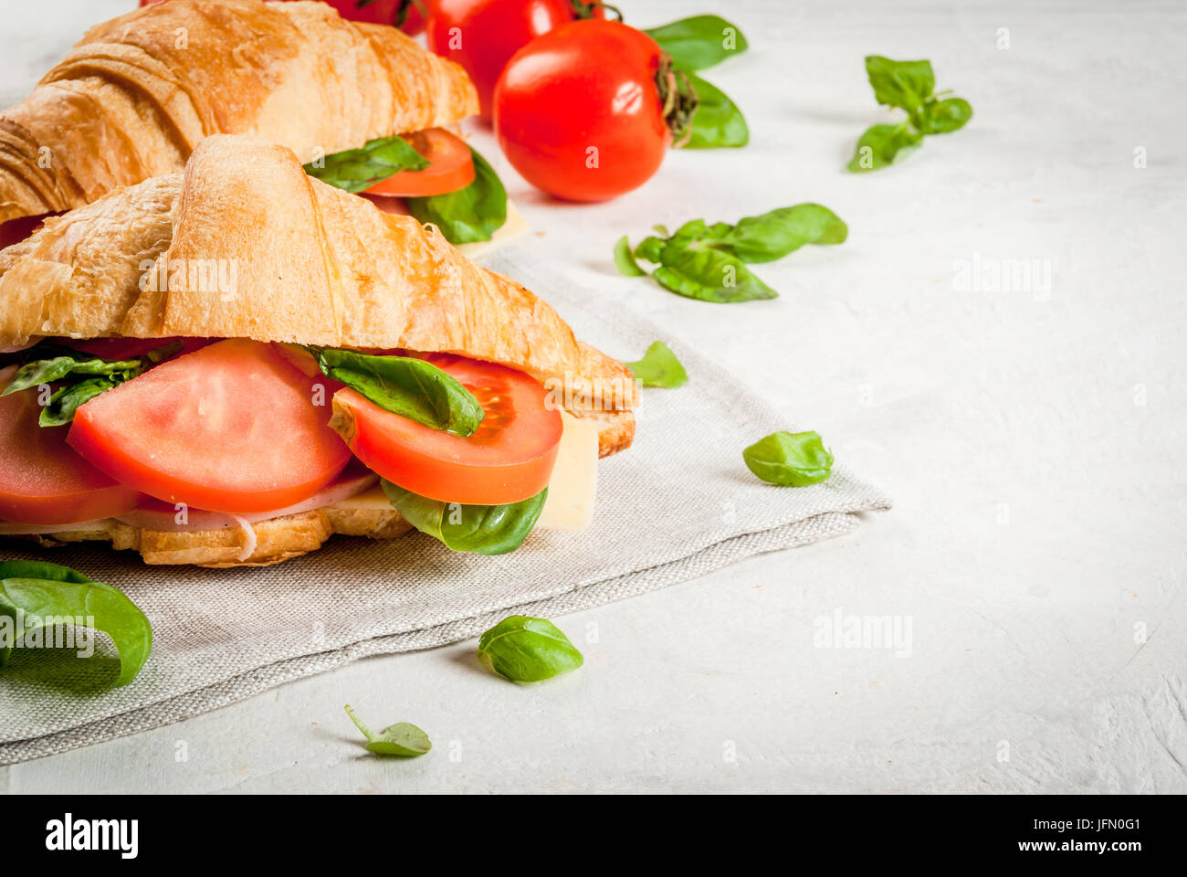 Light and hearty spring breakfast. Croissant with ham, cheese, fresh tomatoes and basil. On a white stone table, - Stock Image