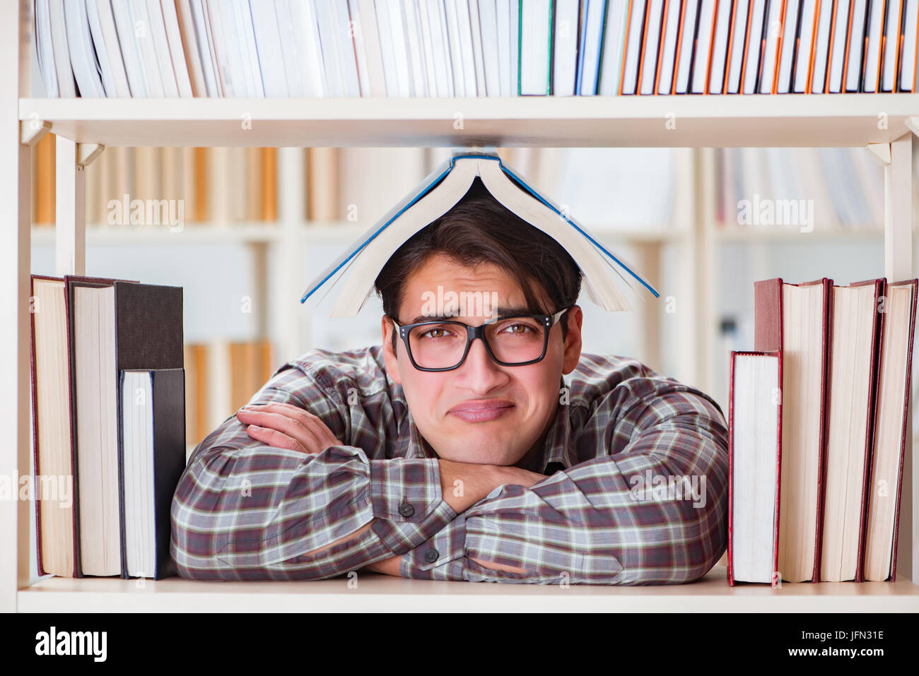 The young student looking for books in college library - Stock Image