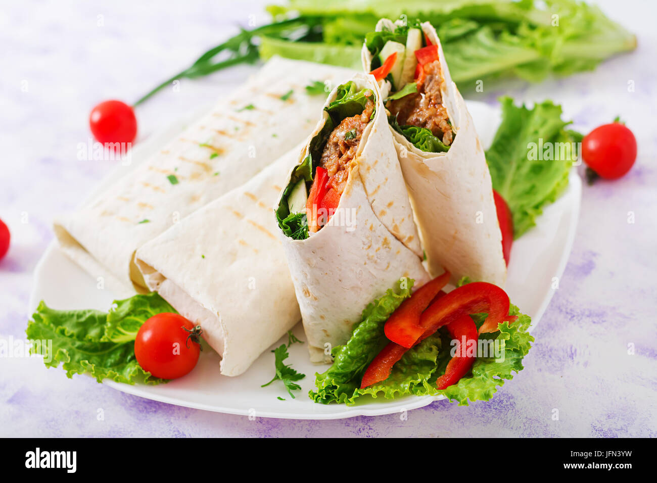 Burritos wraps with minced beef and vegetables on a light background. - Stock Image