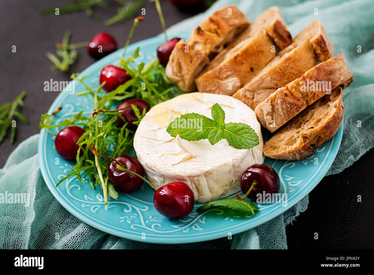 Baked Camembert cheese, toast and arugula salad with  sweet cherries. - Stock Image