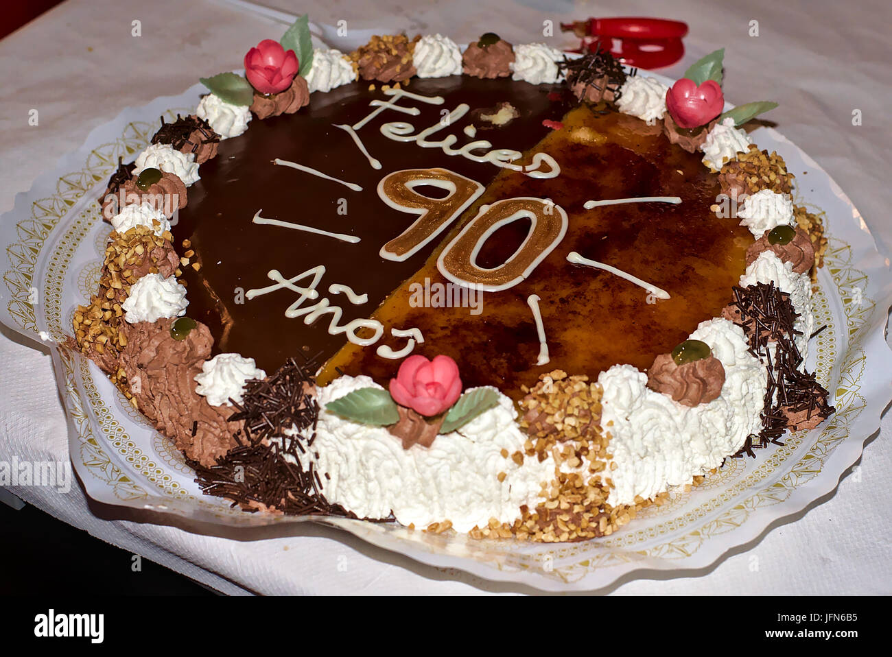 Delicious Two Flavor Birthday Cake With A Happy 90th Celebration As Decoration Made Of Cream Chocolate Fruits And Almonds