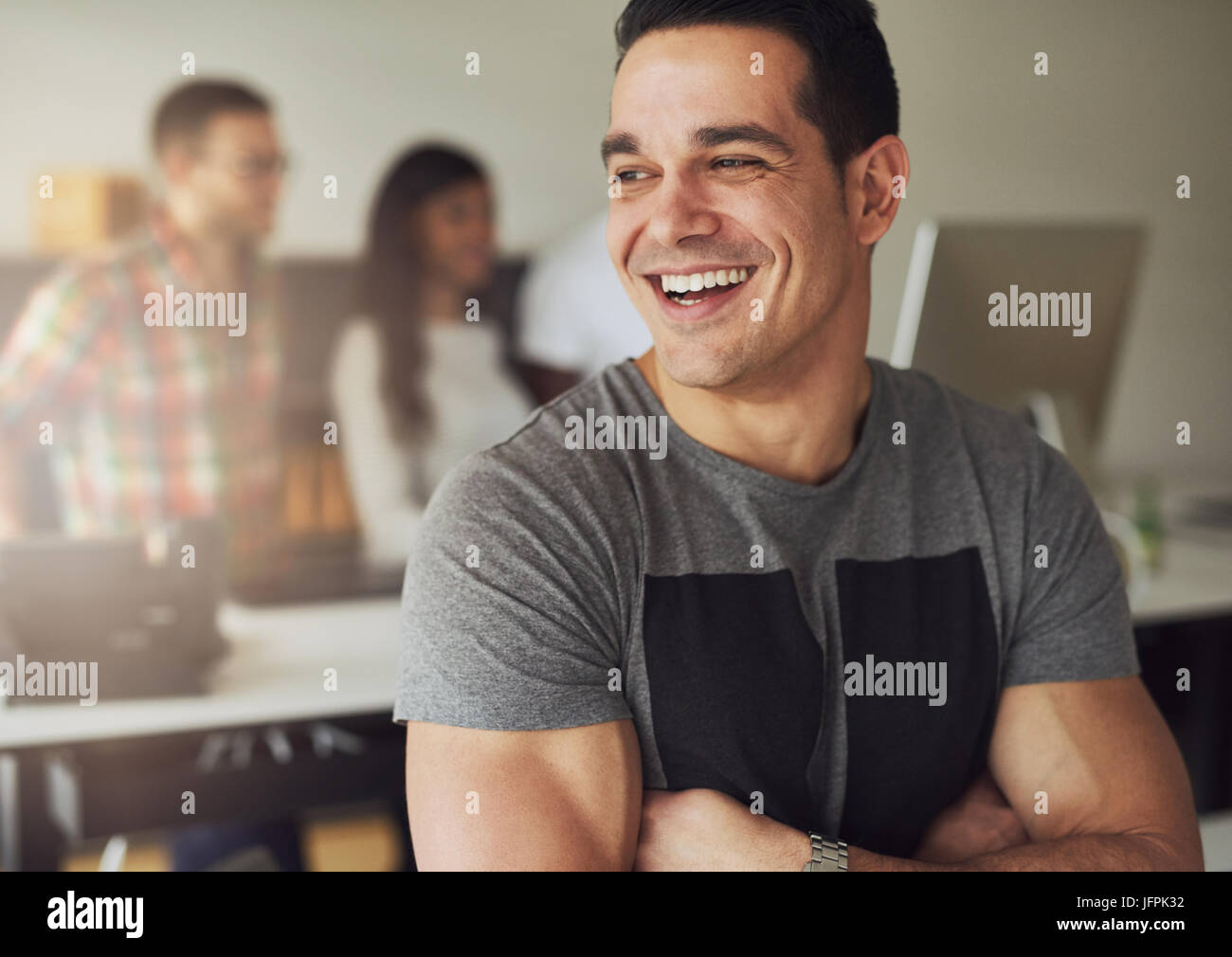 Smiling young confident man with arms crossed standing and looking away in the office. - Stock Image