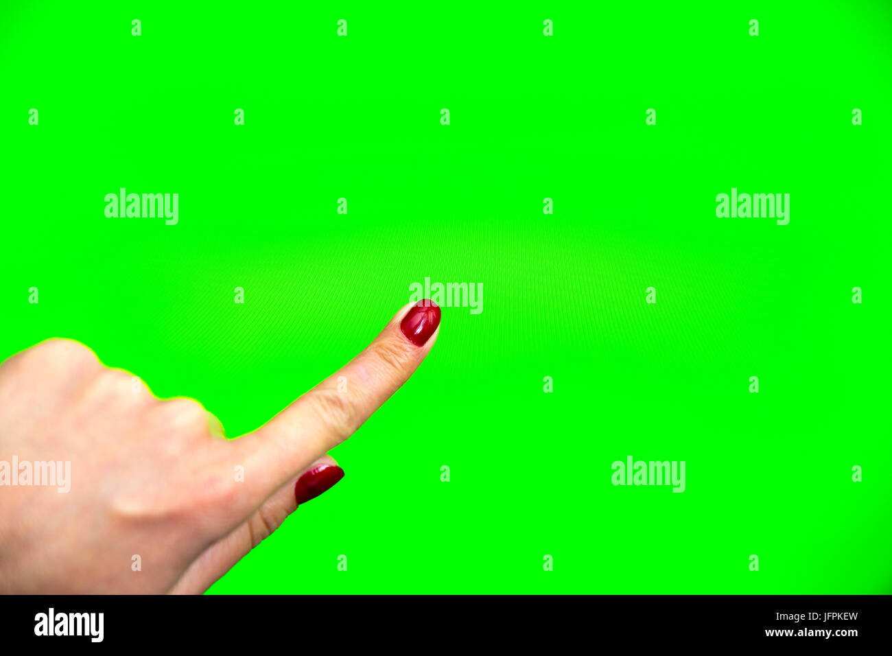 Young woman types and slides on a digital screen. Computer monitor with chroma key screen - green screen. Red nail - Stock Image