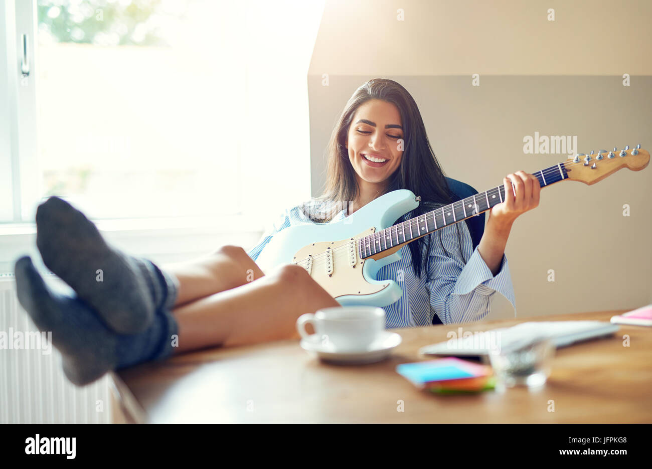 Beautiful girl singing while playing her electric guitar with feet on top of table Stock Photo