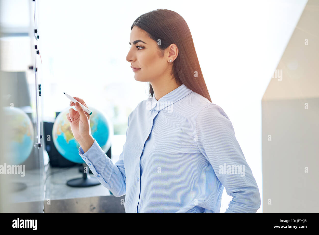 Serious young woman in blue at white board in classroom or small office with globe in background - Stock Image