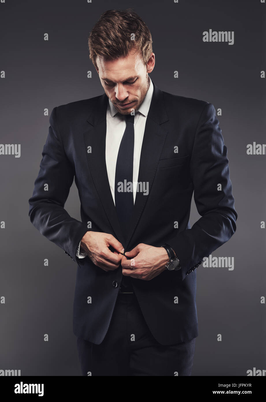 a370bd8f8c Handsome young businessman buttoning up the jacket of a stylish black suit  standing alone in a studio against a grey background
