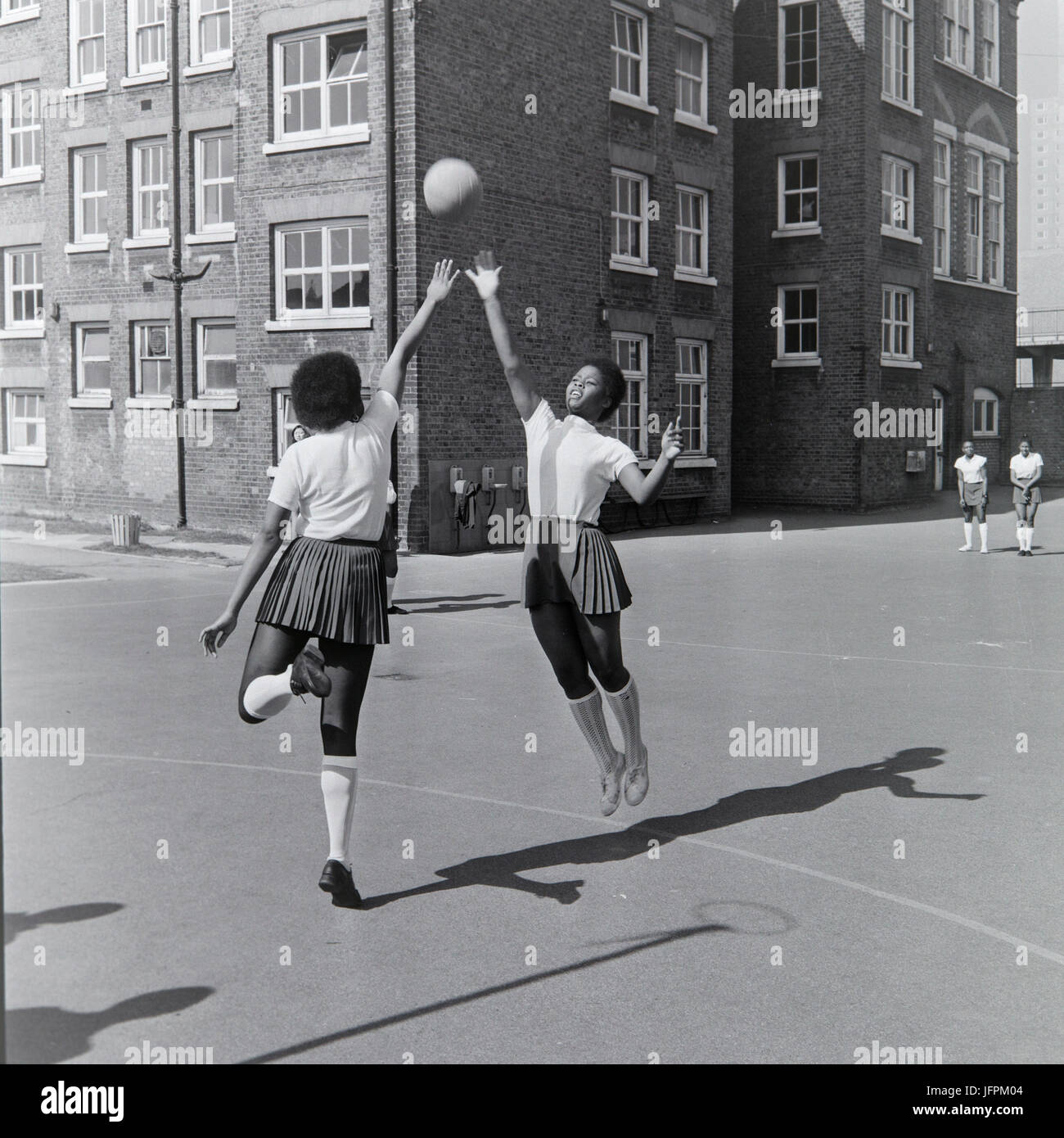 Two black, afro caribbean girls playing netball in London, England, during the 1970s. - Stock Image