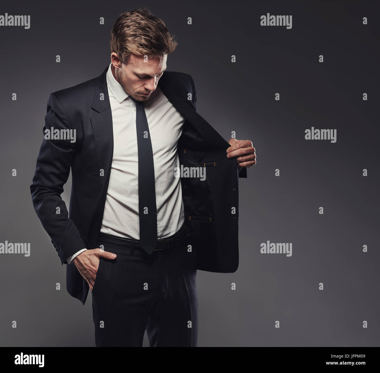 Suave young businessman checking out the jacket of a stylish black suit standing alone in a studio against a grey - Stock Image