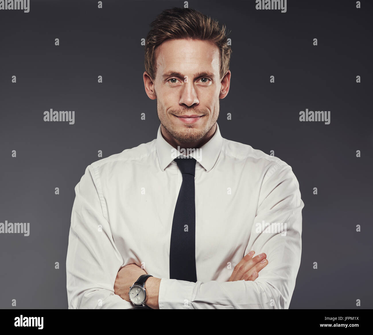 Handsome young businessman wearing a shirt and tie smiling and standing with his arms crossed alone in a studio - Stock Image