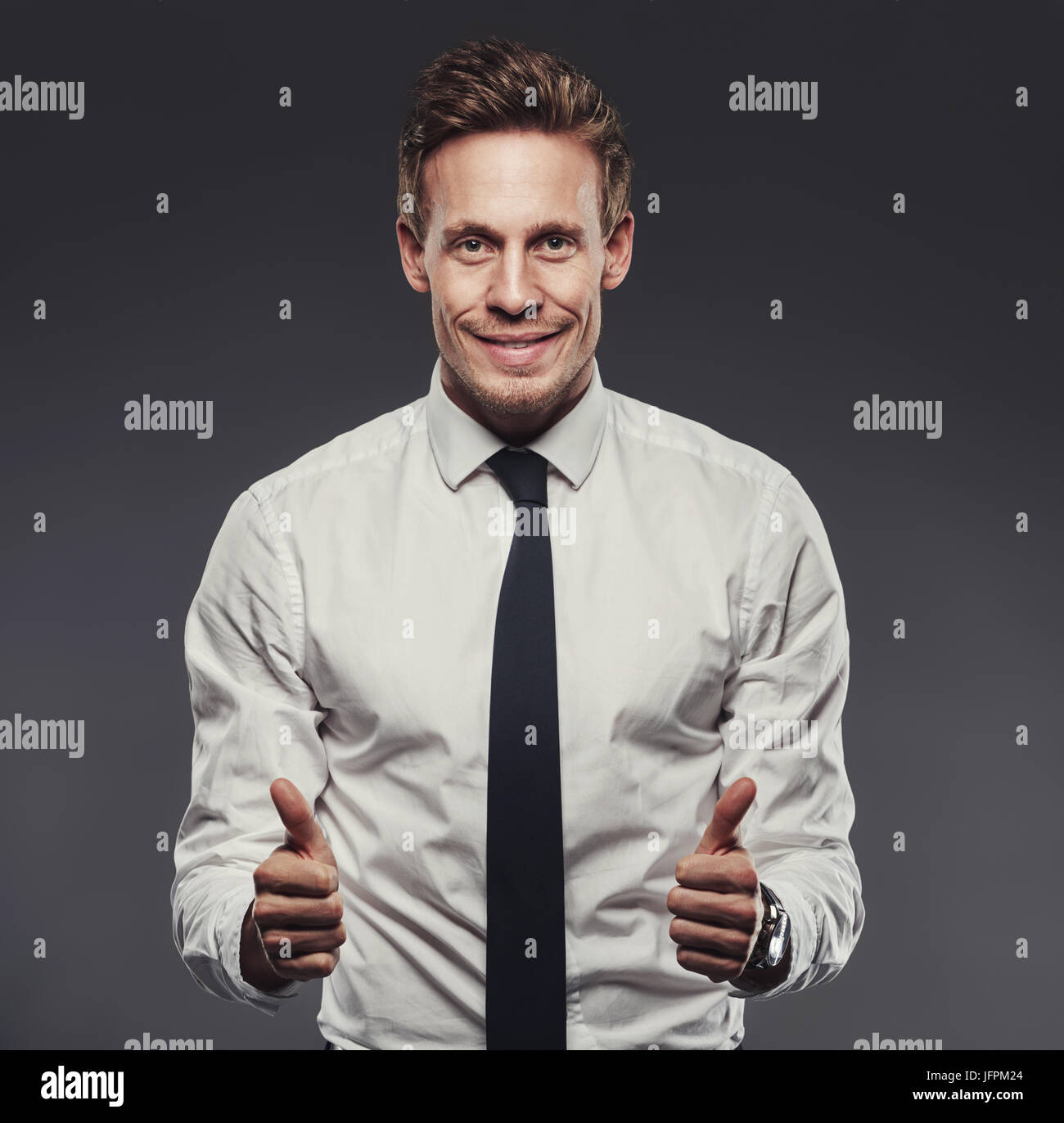 Smiling young businessman wearing a shirt and tie giving an enthusiastic thumbs up while standing alone in a studio - Stock Image