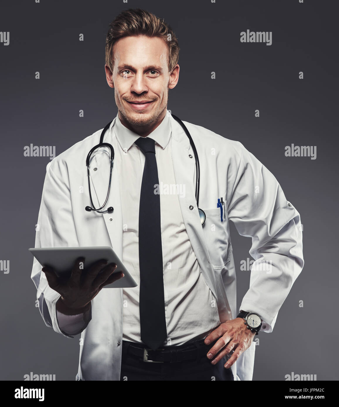 Smiling young doctor wearing a labcoat and holding a digital tablet standing alone in a studio against a grey background Stock Photo