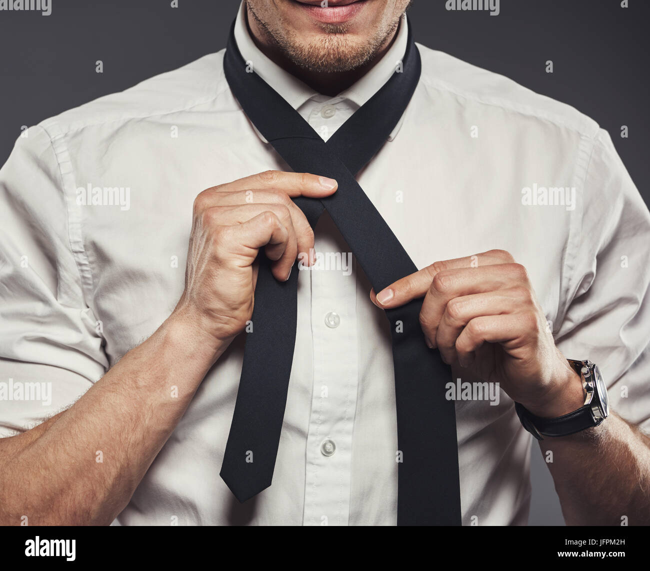 Closeup of a young businessman in a shirt standing in a studio against a grey background tying his necktie - Stock Image