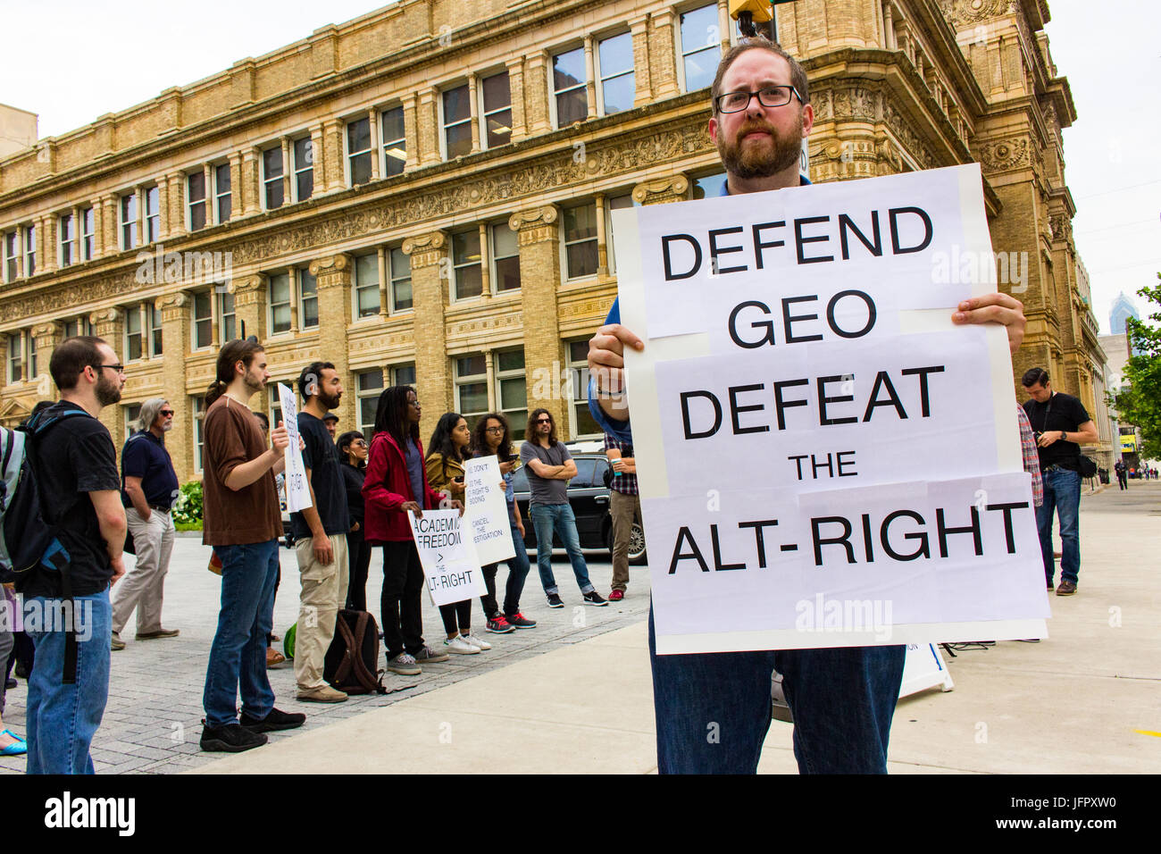 Rob Zilitor, alumnus and veteran, holds a sign during a protest outside Drexell's Randell Hall. Photography - Stock Image