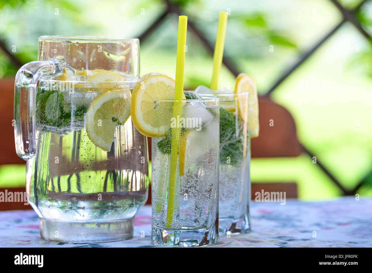 Cool and refreshing drink with lemon, mint and ice in the garden on a hot day. - Stock Image