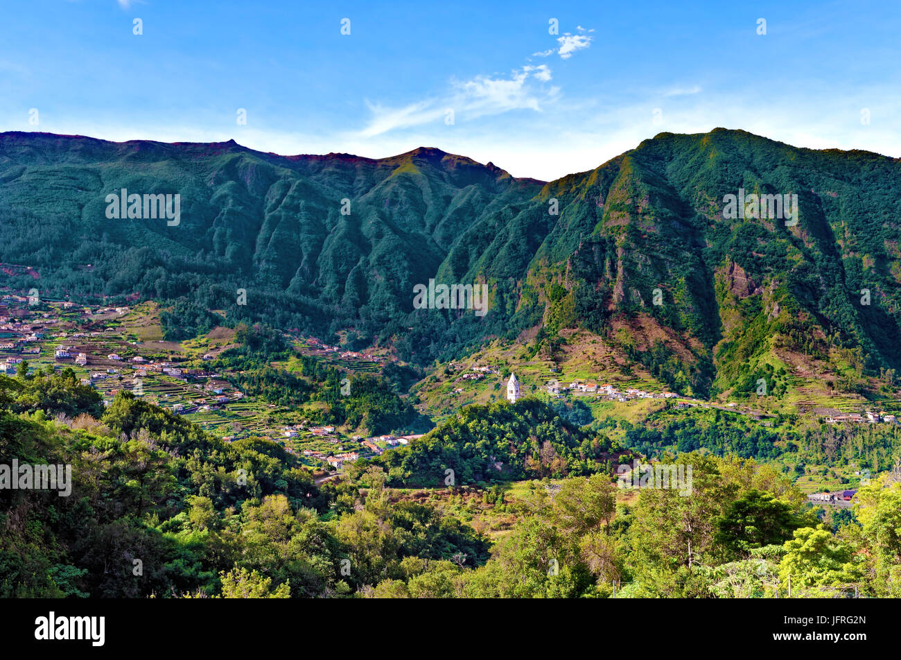 A distant view of a church steeple nestling in the hilly landscape of Madeira - Stock Image