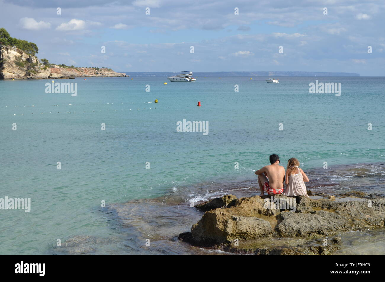 Boy And Girl Sitting On A Rock Of Cala Major Beach In Palma De Stock Photo Alamy
