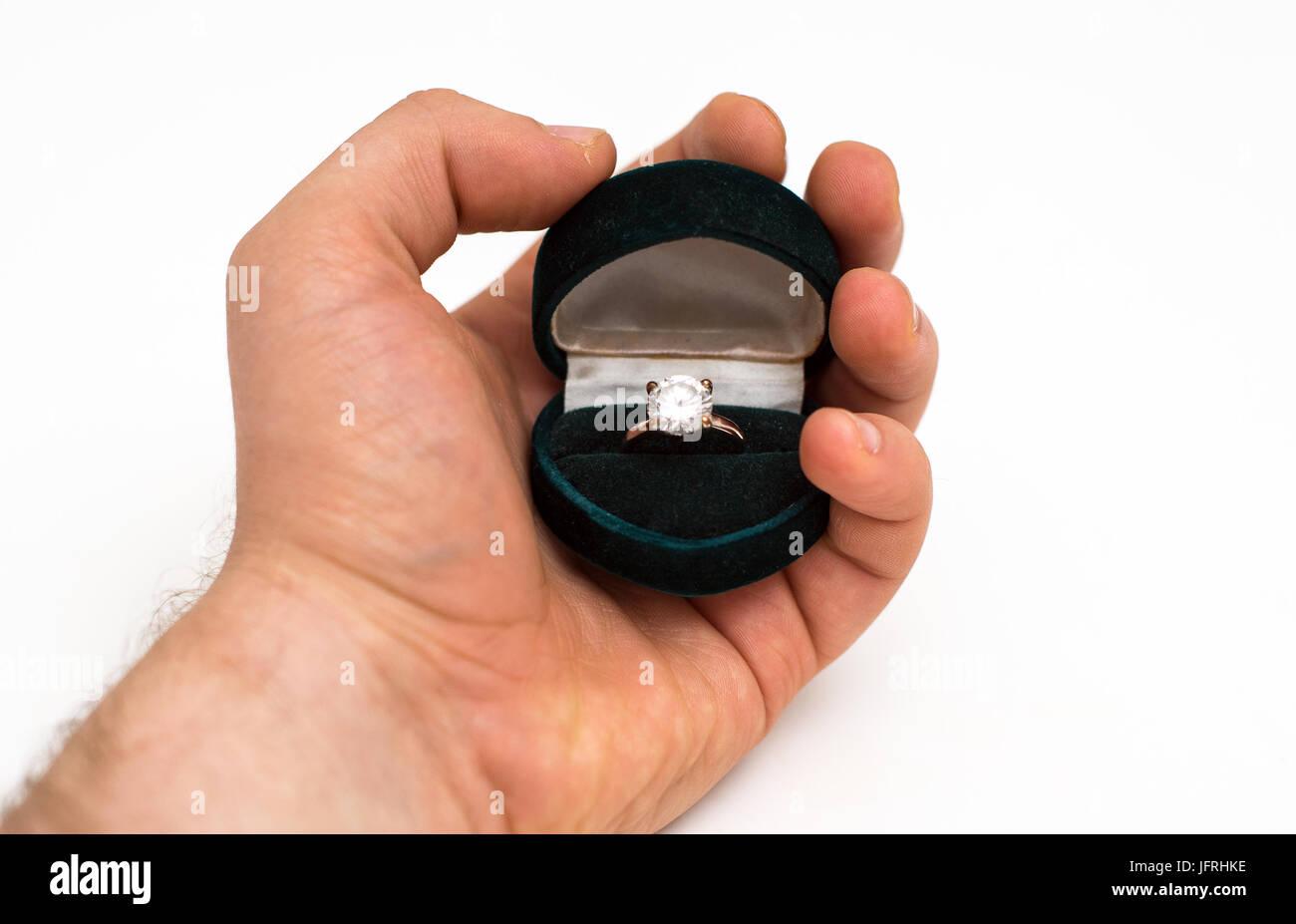Man's hand holding wedding ring with diamond. - Stock Image