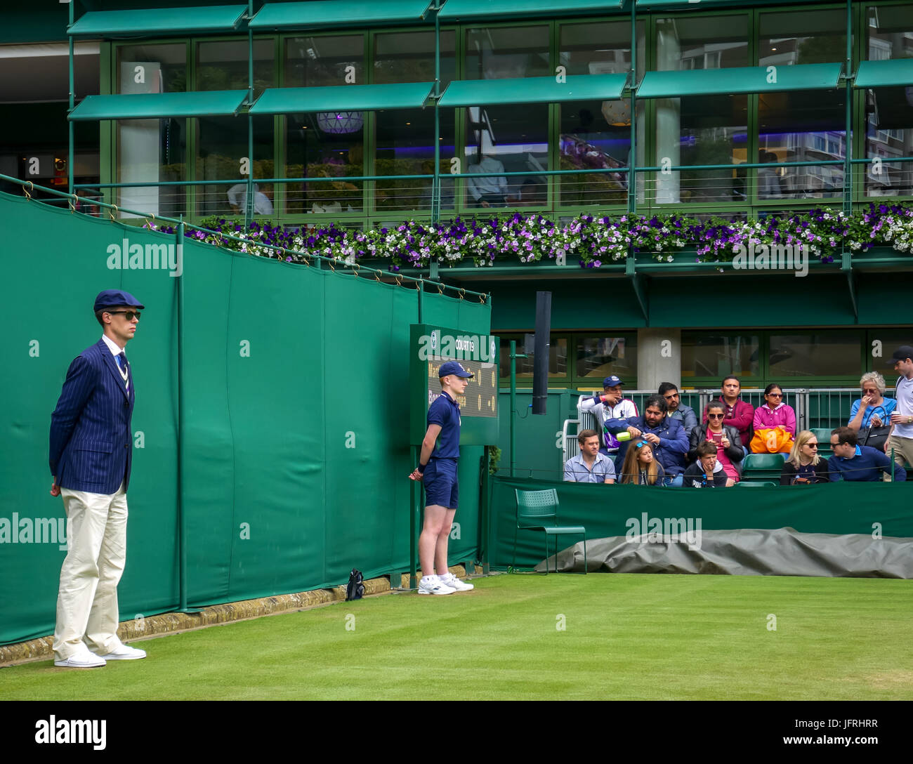 Wimbledon line judge and ball boy standing to attention during tennis match on Court 19, AELTC, Wimbledon 2016, Stock Photo