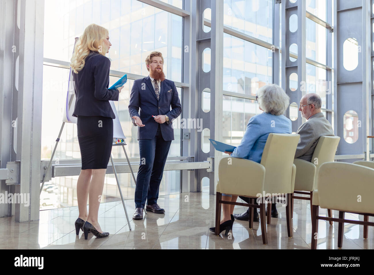 Business people making presentation to senior couple at business center, investment, investment concept - Stock Image