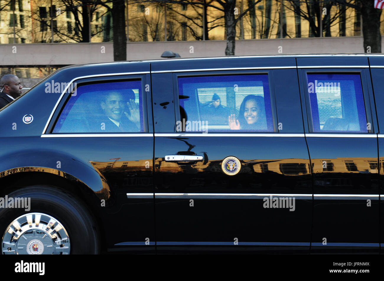 President Barack Obama and his daughter, Sasha, wave to the crowd from inside the presidential limousine as it makes - Stock Image