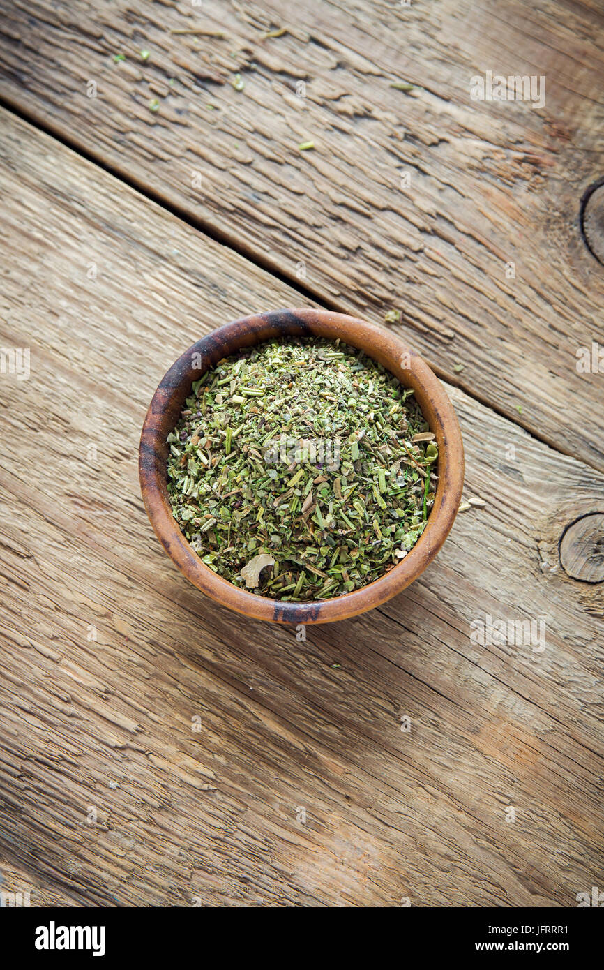 Mixed Italian Herbs Seasoning on wooden background, copy space. Dried Herbs Seasoning, healthy ingredient for cooking. - Stock Image