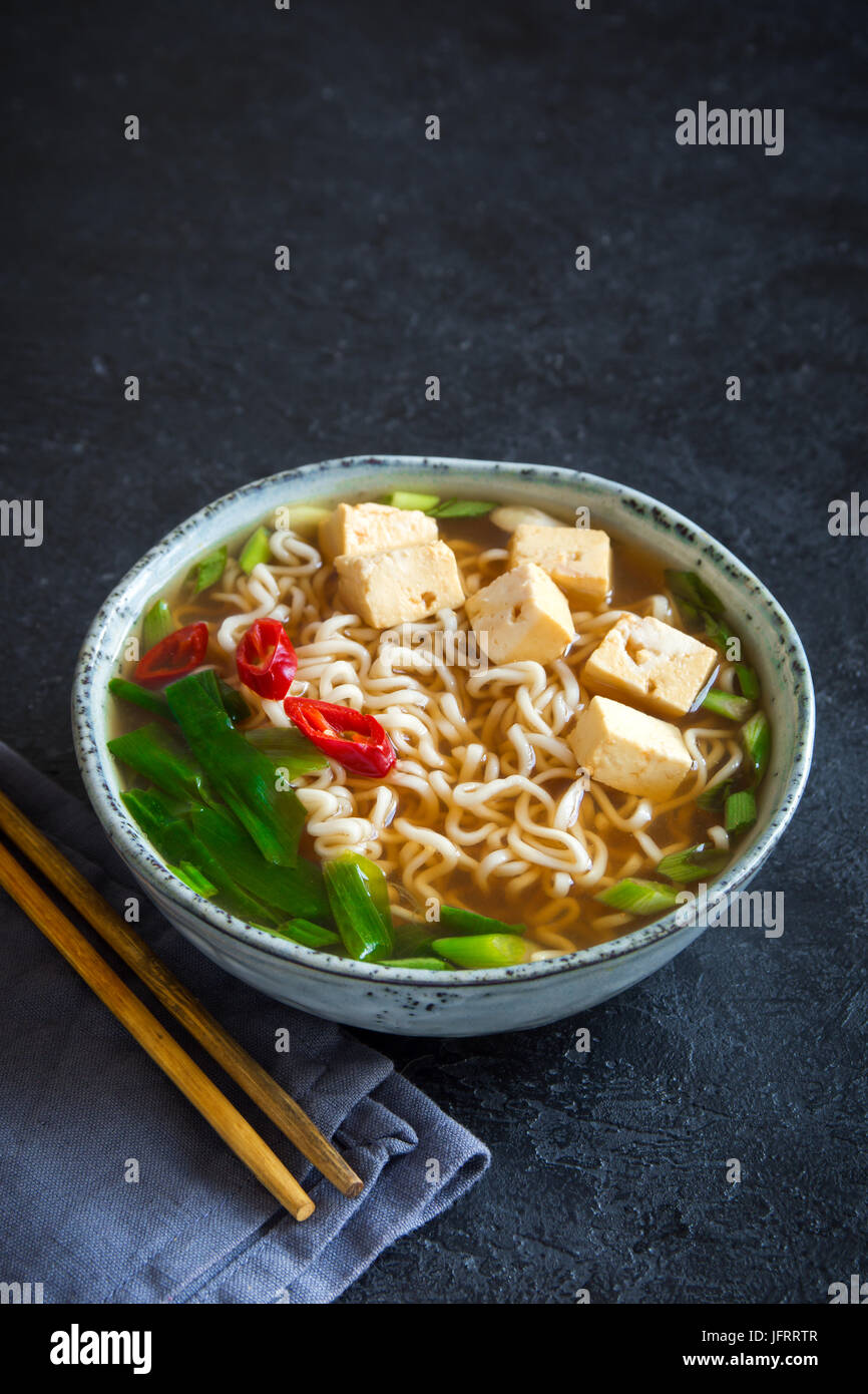 Japanese ramen soup with tofu on dark stone background. Miso soup with ramen noodles and tofu in ceramic bowl, asian - Stock Image