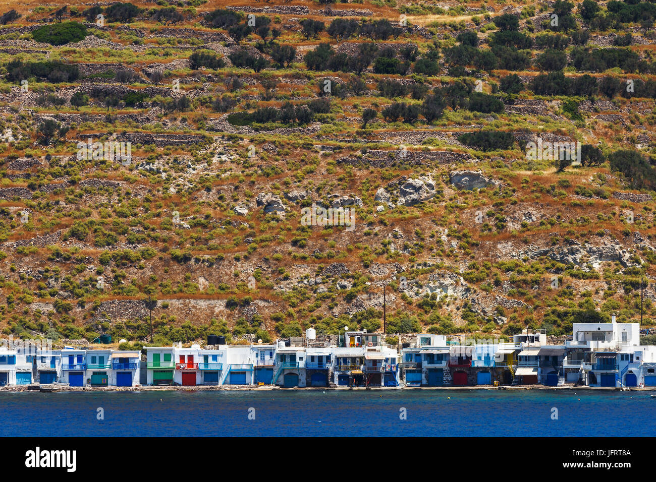 Klima village on the coast of Milos island as seen from the ferry. - Stock Image