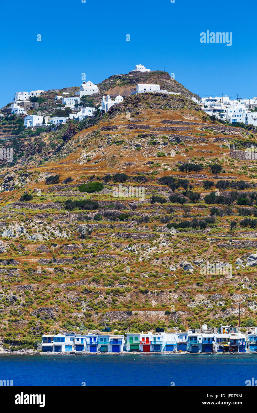 Klima and Plaka villages on the coast of Milos island as seen from the ferry. - Stock Image