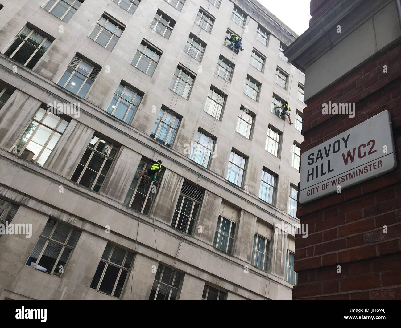 High rise window cleaners are working on a building in Central London by the Savoy Hill street in WC2. Stock Photo