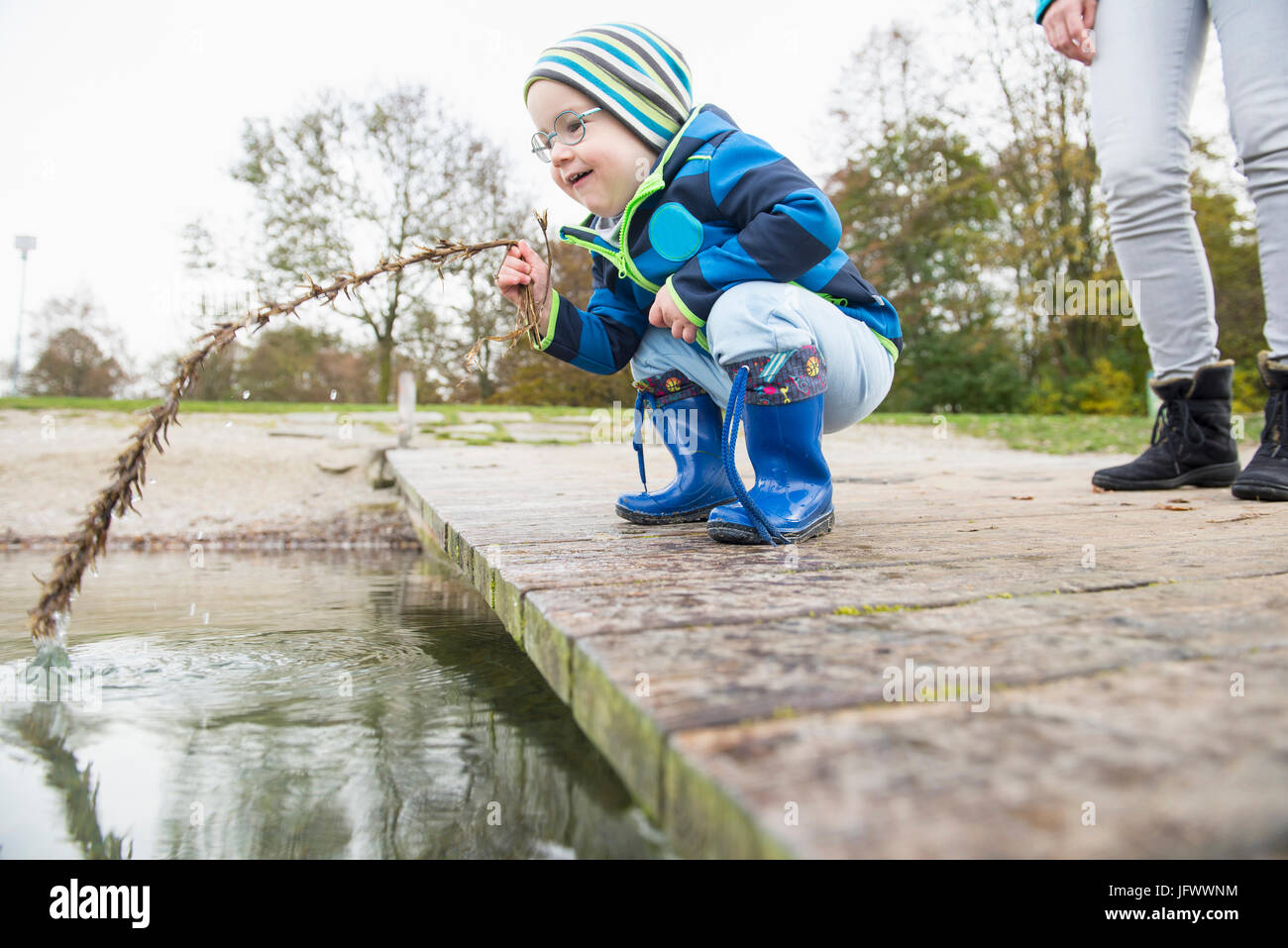 Little boy crouching on a landing pier on lake holding branch into water with his mother in background - Stock Image