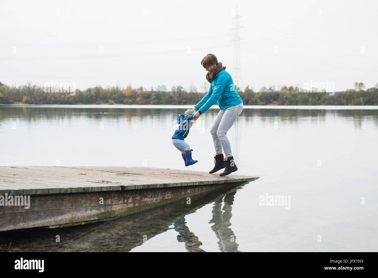 Mother and son jumping hand in hand on a landing stage at a lake in the autumn - Stock Image