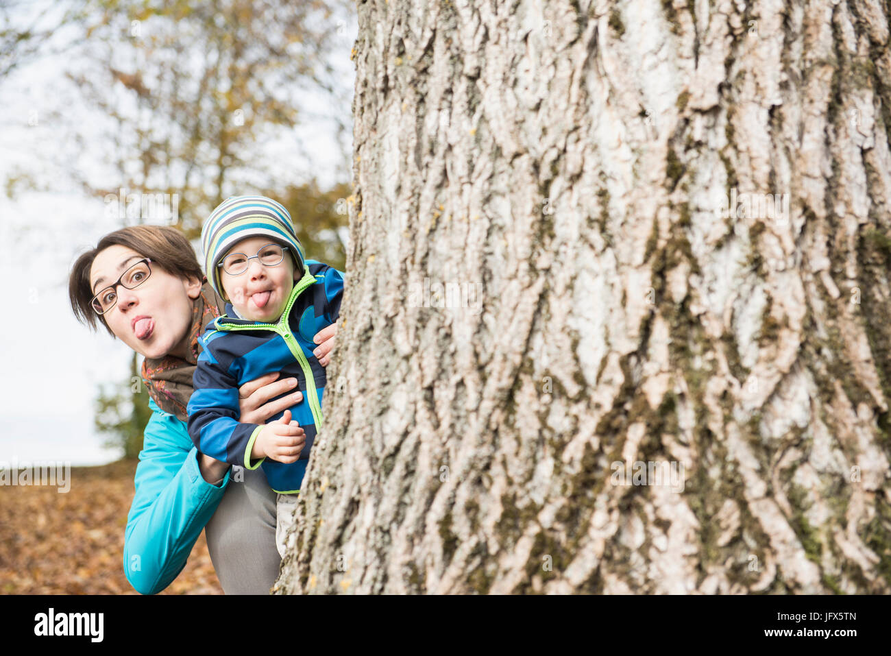 Mother and son sticking out heir lounges looking out behind of big tree in autumn scenery - Stock Image