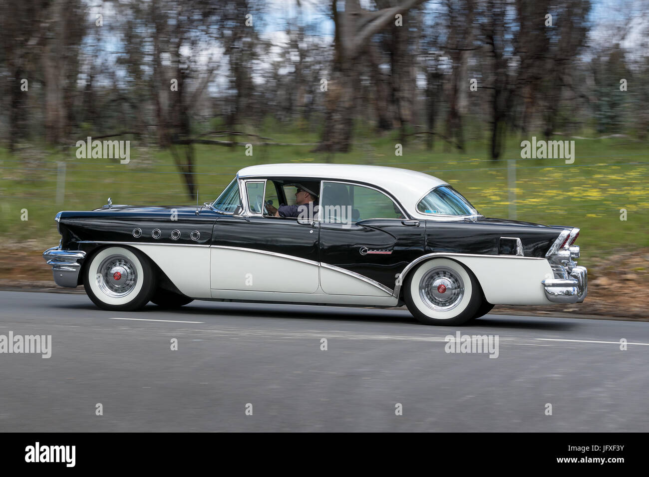 vintage 1955 buick century sedan driving on country roads near the