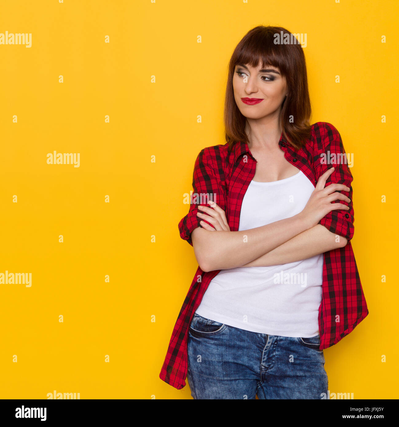 Grimacing young woman in red lumberjack shirt and jeans posing with arms crossed and looking away. Three quarter - Stock Image